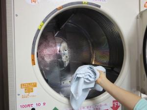 乾燥機ドラムに洗濯物を入れる
